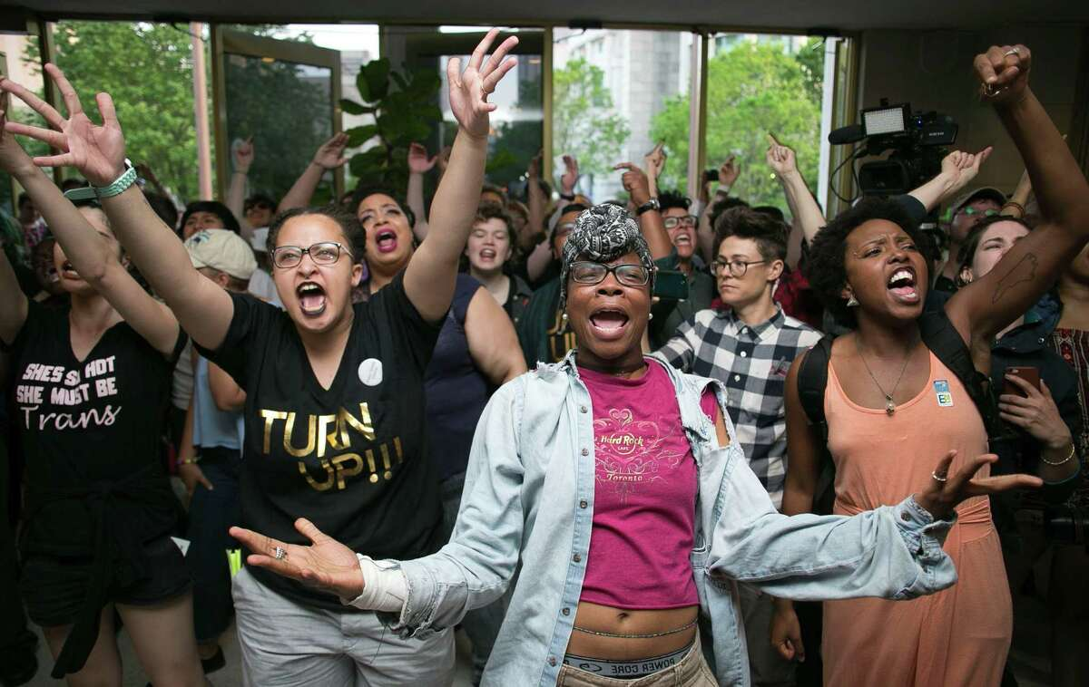 Krys Didtrey, left, and Gloria Merriweather, center, of Charlotte, N.C., lead chants against the law limiting transgender bathroom access during a protest in the State Legislative Building's lobby. in opposition to House Bill 2 during a protest in the lobby of the State Legislative Building in Raleigh, N.C. on Monday April 25, 2016. A large group of people starting chanting in the lobby moment after the House adjourned for the evening. (Robert Willett/The News & Observer via AP) MANDATORY CREDIT