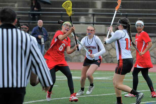 Greenwich Erika Bloes (6) fires a shot on goal past Stamford Mackenzie Brown (15) during a FCIAC league game at Stamford High School on April 26, 2016. Greenwich defeated Stamford 15-7.
