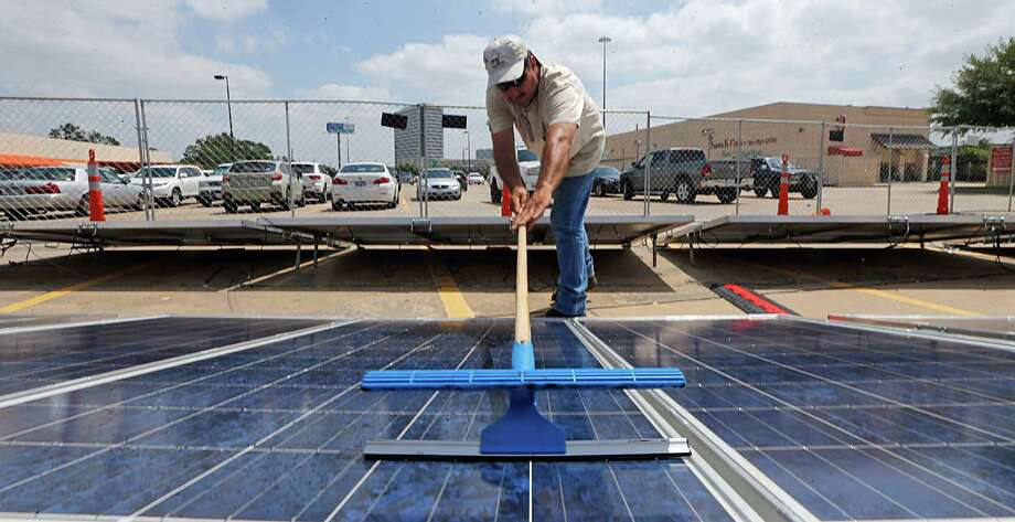 NRG's Tom Jewell cleans a solar panel as NRG Energy's Power2Serve relief vehicle and trailer visit the area. Photo: James Nielsen, Staff / © 2016  Houston Chronicle