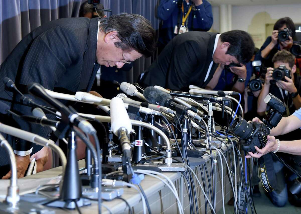 "Mitsubishi Motors president Tetsuro Aikawa, left, bows in apology Tuesday at a news conference at the transport ministry in Tokyo. ""I feel a great responsibility,"" Aikawa said of the company's gas mileage falsehoods. PHOTO / TOSHIFUMI KITAMURATOSHIFUMI KITAMURA/AFP/Getty Images"