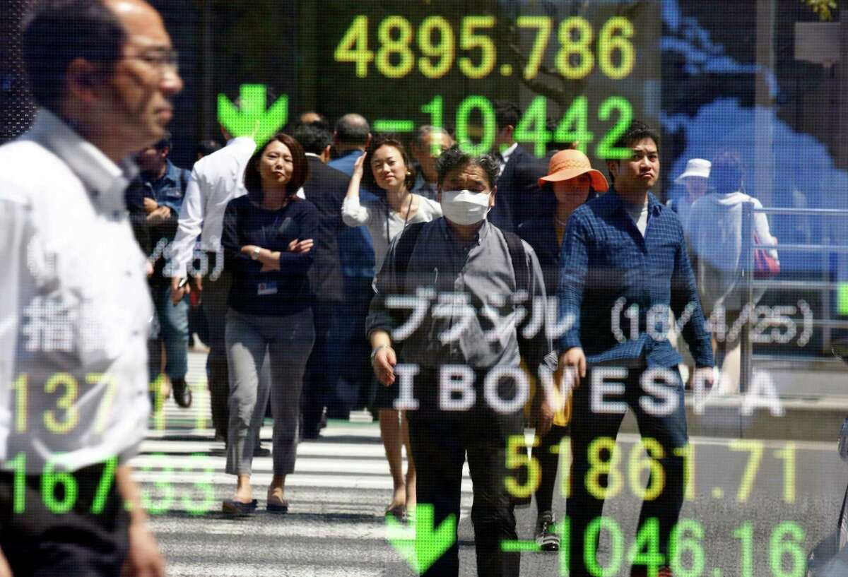 People are reflected on the electronic board of a securities firm in Tokyo, Tuesday, April 26, 2016. Asian stock markets fell Tuesday ahead of U.S. Federal Reserve and Bank of Japan policy meetings, as commodity prices ran out of steam, dragging on big miners. (AP Photo/Shizuo Kambayashi)