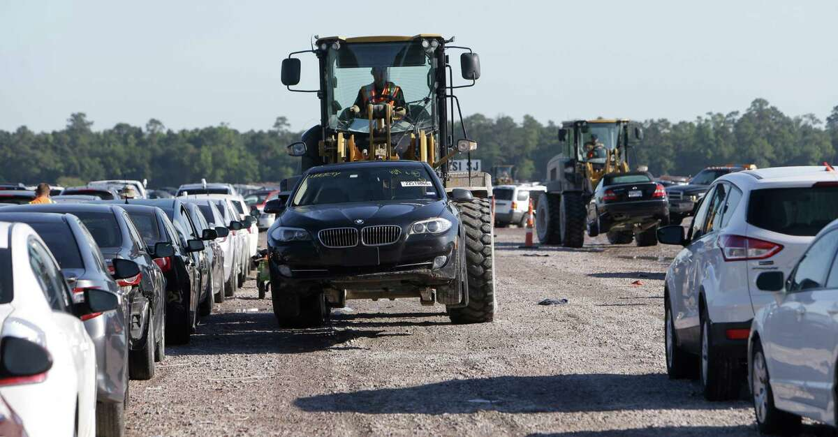 Cars are shown being moved at an auto salvage yard Friday, April 22, 2016, in Houston where many flooded cars are stored. An increase in auto sales is expected as owners replace their totaled vehicles. ( Melissa Phillip / Houston Chronicle )