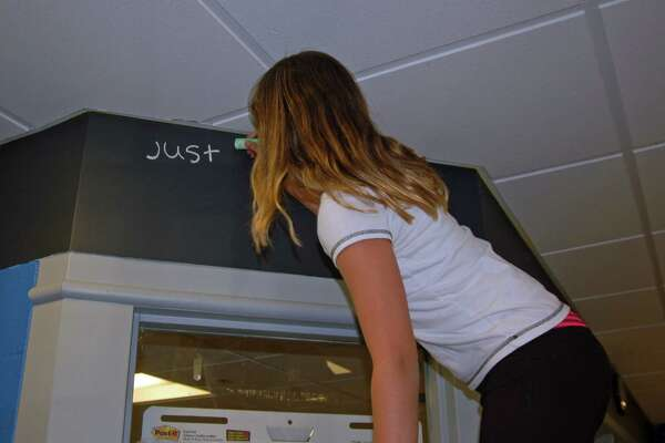"""Eleven-year-old Isabella Silvadomingos is the first person to mark the newly renovated and updated teen room at the Boys and Girls Club of Greenwich with chalk. The full text of what she wrote is """"Just cause the world is turning doesn't mean you have to turn on the world."""""""