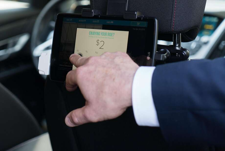 Hall demonstrates how his passengers would tip by using a tablet in his car. He also texts riders before picking them up. Photo: James Tensuan, Special To The Chronicle