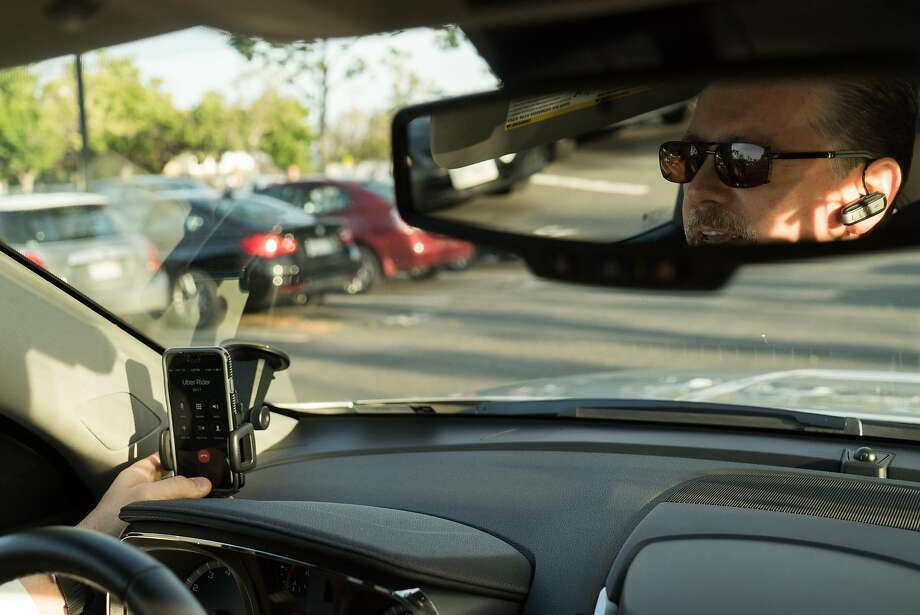 Uber driver Mark W. Hall heads through San Jose. The company's drivers can now inform passengers that tipping is allowed, which Hall does in a variety of ways, including a sign on his dashboard. Photo: James Tensuan, Special To The Chronicle