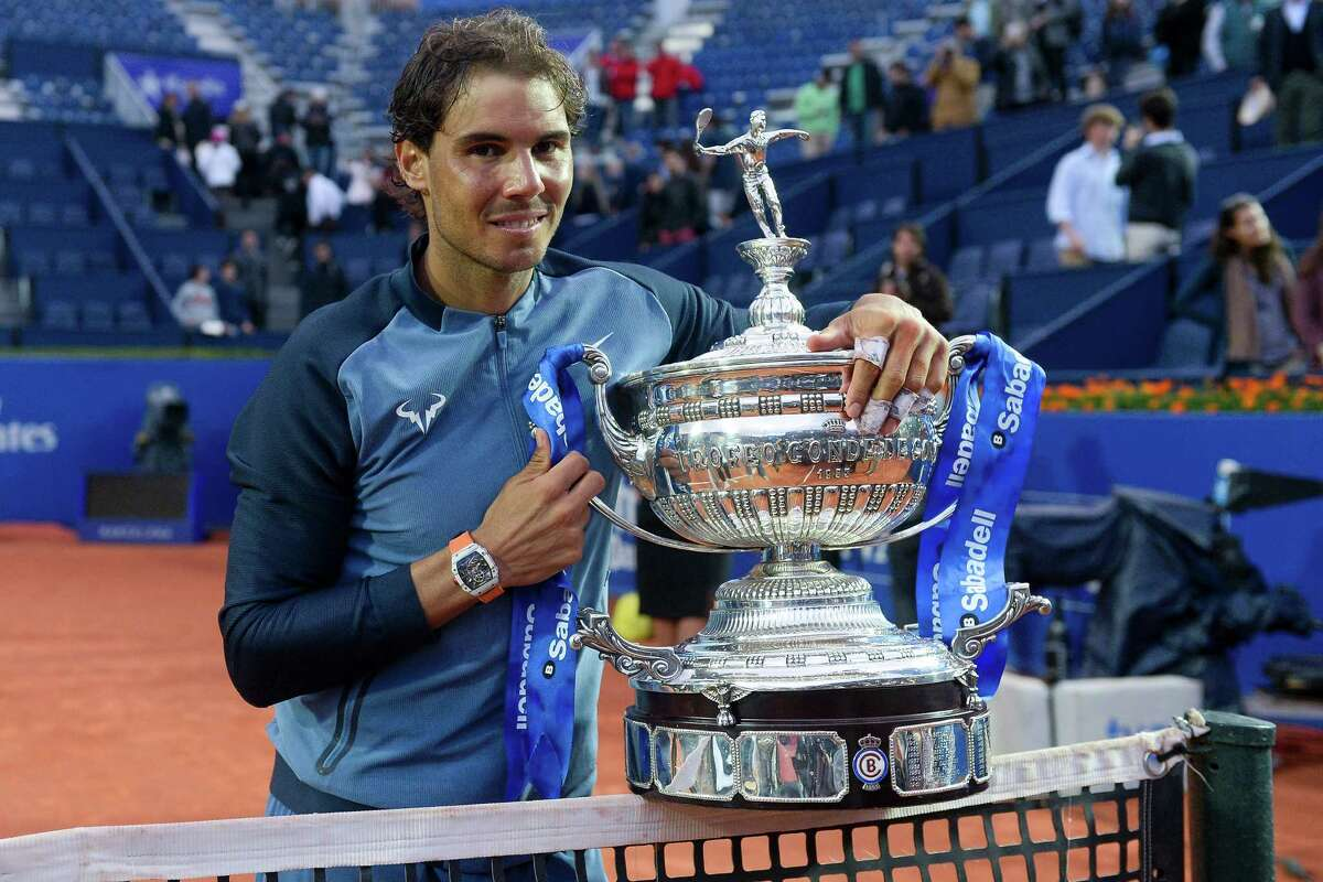 """Spanish tennis player Rafael Nadal poses with his trophy as he celebrates his victory over Japanese tennis player Kei Nishikori after the final of the ATP Barcelona Open """"Conde de Godo"""" tennis tournament in Barcelona on April 24, 2015. Rafael Nadal equalled Argentine legend Guillermo Vilas's record of 49 clay-court titles with his ninth Barcelona Open after overcoming defending champion Kei Nishikori 6-4, 7-5 today. / AFP PHOTO / JOSEP LAGOJOSEP LAGO/AFP/Getty Images"""