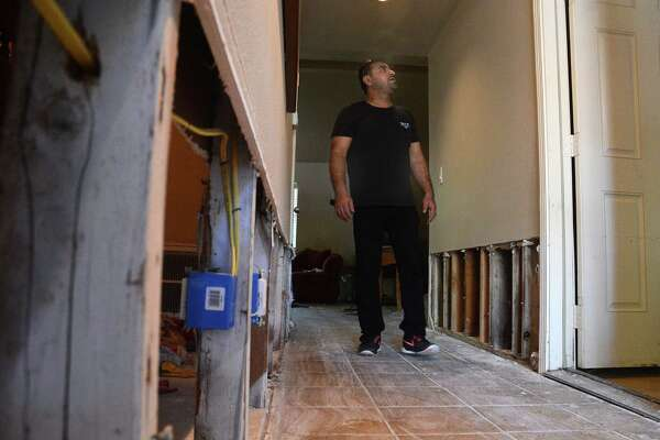 Ahsan Khan checks for flood damage in his home in the Timber Lakes-Timber Ridge subdivision, south of The Woodlands. Khan has already removed gypsum wallboard along the hallway that was damaged by the April 18 floods that hit the area.