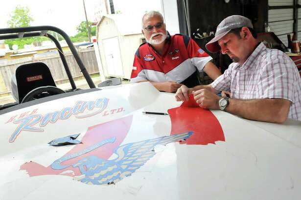 Wayne Barber, left, of Port Neches watches as Keith Anderson of Hightech Signs strips Barber's Tri-Hull boat of graphics prior to applying the new ones in time for this weekend's Thunder on the Neches races in Port Neches. Barber, who won the Tri-Hull competition at last year's event, will be competing again this weekend. (Mike Tobias/The Enterprise)