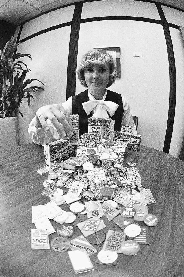 FILE - Sue Reedquist shows some of the 400 prizes she selects for each day's production of Cracker Jacks at the company plant in Chicago. October 28, 1978.  The mixture of sweetened popcorn and peanuts is packed into boxes in one part of the plant, and the prizes she selects are placed in each box by hand in another part of the plant. Photo: Fred Jewell, AP