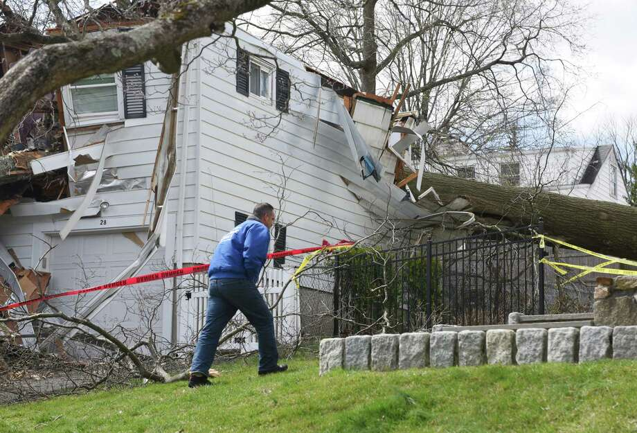 High winds caused a tree to fall through a house on Elmbrook Drive in Stamford, Conn. on April 3, 2016. In mid-April 2016, Gov. Dannel P. Malloy announced stiffer building codes are on the way for new construction and renovations, to include impact-resistant windows and ties designed to tether roofs more securely to structures. Photo: Tyler Sizemore / Hearst Connecticut Media / Greenwich Time
