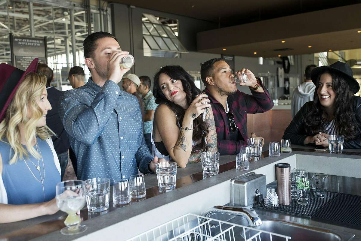 Marisa Cabrera (center) and Roger Cabrera (second from right) celebrate both their birthdays with friends in the tasting room at St. George Sprits in Alameda, Calif., on Sunday, April 24, 2016. The distillery has a tasting room and also gives tours.