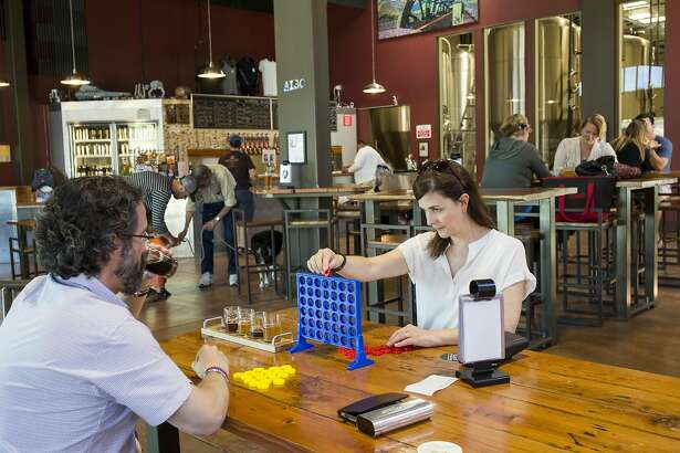Rosemary Jordan plays one of the several games available to visitors of the tasting room at Alameda Island Brewing Company with Kevin Jordan (left) in Alameda, Calif., on Sunday, April 17, 2016. The microbrewery focuses on fine craft beers.