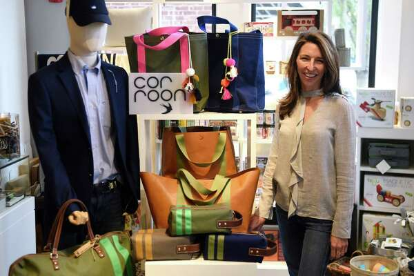 Corroon Founder and CEO Kelly Corroon poses by her collection of Corroon bags now available at Back 40 Mercantile in Old Greenwich, Conn. Tuesday, April 26, 2016.