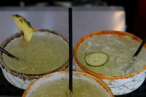 """Drinks made from infused spirits at The Frutería-Botanero on South Flores Street include the """"pepino"""" margarita (top, right) with a cucumber infusion, the gin drink infused with fresno pepper and orange skin (center, bottom) and the Piña Mezcal infused with orange and pineapple (top, left)."""