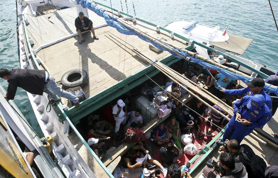 FILE - In this May 12, 2013 file photo, Iranian asylum seekers who were caught in Indonesian waters while sailing to Australia sit on a boat at Benoa port in Bali, Indonesia. Papua New Guinea's Supreme Court on Tuesday, April 26, 2016 ruled that Australia's detention of asylum seekers at a facility on the country's Manus Island is unconstitutional. The Pacific island nation's ruling could jeopardize Australia's divisive policy of refusing to accept any asylum seekers who attempt to reach its shores by boat. The country pays Papua New Guinea and the tiny Pacific island nation of Nauru to hold them in detention camps instead. (AP Photo/Firdia Lisnawati, File) Photo: Firdia Lisnawati, Associated Press