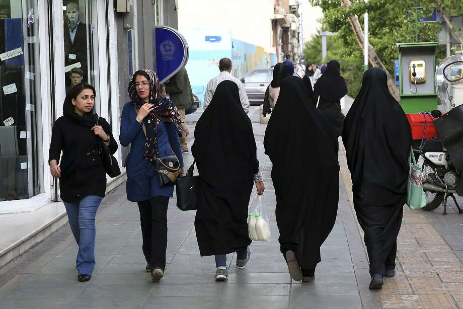 Women walk along a sidewalk in downtown Tehran. Critics fear a new police division will enforce a dress code that requires women to be modestly covered from head to toe. Photo: Vahid Salemi, Associated Press
