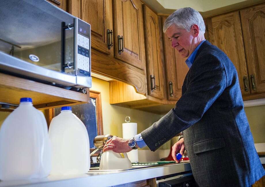 Gov. Rick Snyder fills jugs with filtered tap water at a Flint home. Snyder wants his state to become a national model for monitoring lead levels in water. Photo: Jake May, Associated Press