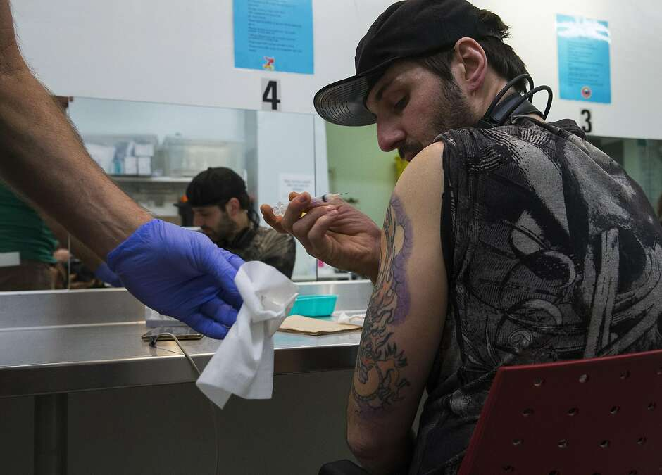 Mike O'Reilly injects his daily dose of drugs in a heroin main tenance program at a clinic in Vancouver, British Columbia.