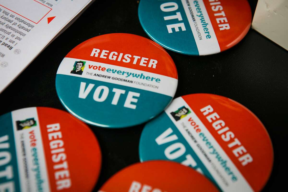 Pins encouraging students to register to vote sit on a table at UC Berkeley, in Berkeley, California, on Wednesday, April 27, 2016.