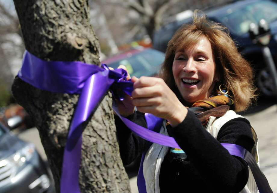 Celebrating Hope 2015 volunteeer Joy Mindlin, of Stamford, places a purple bow on a tree in front of the Board of Education building in Greenwich. The 2016 benefit will take place Friday night at the Delamar. Photo: Tyler Sizemore / Tyler Sizemore / Greenwich Time