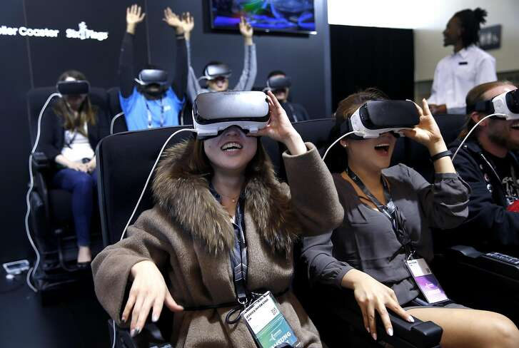 Jessica Kim (left) and Hayden Kim take a virtual roller coaster ride on the Samsung VR stage at the Samsung Developer Conference in San Francisco, Calif. on Wednesday, April 27, 2016.