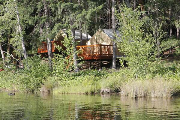 From a boat on Lewiston Lake, the view of the shoreline camping cabins at Mary Smith Campground, Trinity County