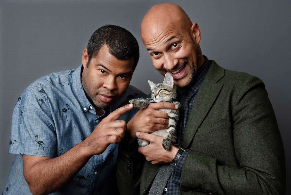 """In this April 23, 2016 photo, Jordan Peele, left, and Keegan-Michael Kay hold a ten-week-old tabby as they pose for a portrait to promote their film, """"Keanu,"""" at The Beverly Hilton Hotel in Beverly Hills, Calif. (Photo by Chris Pizzello/Invision/AP) ORG XMIT: NYET282"""