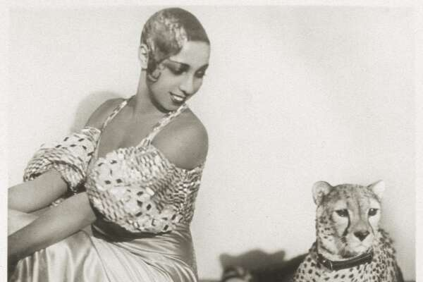 Portrait of American cabaret entertainer Josephine Baker (1906 - 1975) as she sits with her pet cheetah, Chiquita, early 1930s.