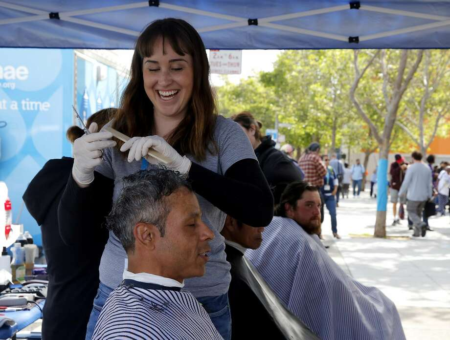 Heather Knowles gives a haircut to William Ortiz during the Pop-Up Care Village outside the Main Library. Photo: Connor Radnovich, The Chronicle
