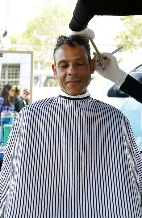 William Ortiz gets a haircut from Heather Knowles during the Pop-Up Care Village event outside the Main Public Library in San Francisco, California, on Tuesday, April 26, 2016. Photo: Connor Radnovich, The Chronicle