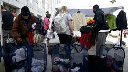 People search through donated clothes hanging and in hampers and use suitcases to carry the clothing during the Pop-Up Care Village event outside the Main Public Library in San Francisco, California, on Tuesday, April 26, 2016.