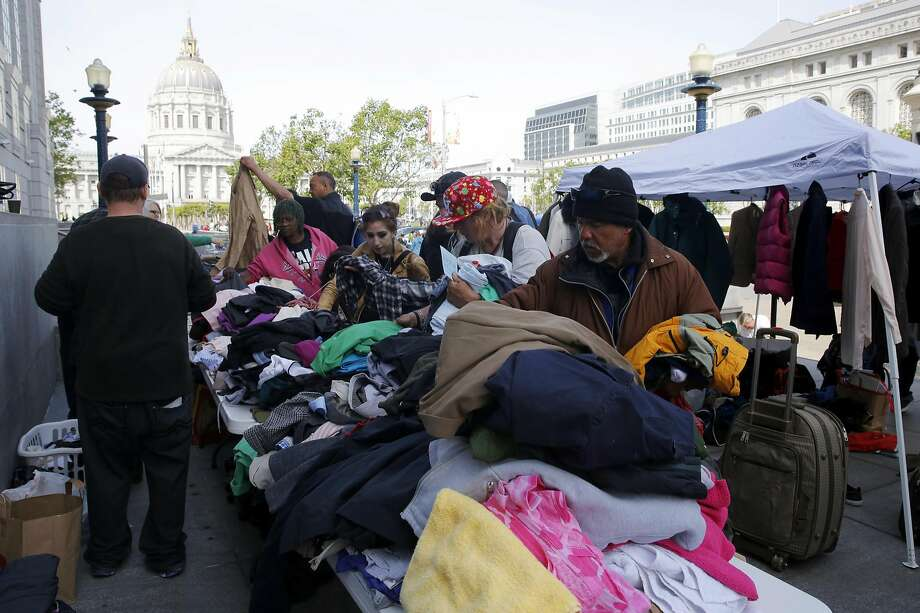 Donated clothing and other items are available for the homeless at the Pop-Up Care Village outside San Francisco's Main Library. Photo: Connor Radnovich, The Chronicle