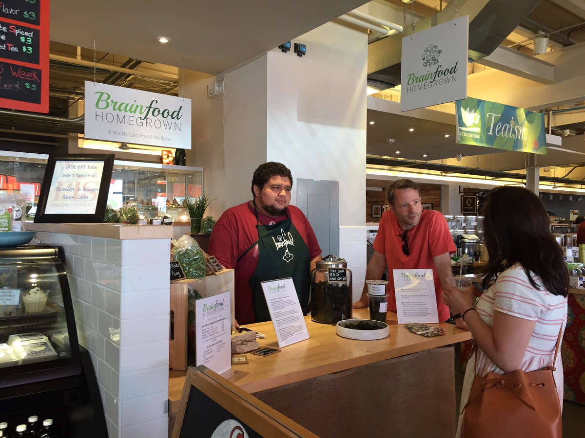 Brainfood's Francisco Rivera, center, talk with a customer at Union Market in D.C.