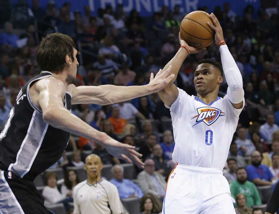 Oklahoma City Thunder guard Russell Westbrook (0) shoots in front of San Antonio Spurs center Boban Marjanovic, left, in the first quarter of an NBA basketball game in Oklahoma City, Saturday, March 26, 2016. Photo: Sue Ogrocki /AP / AP