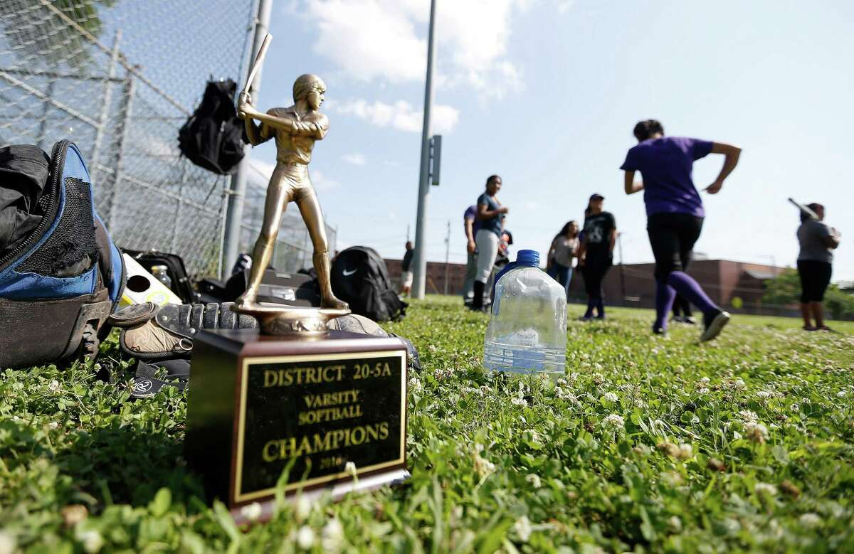 The team's District 20-5A Varsity Softball Championship trophy sits next to the girl's backpacks during the Davis High School softball team practice, Wednesday, April 27, 2016, in Houston. The team was forced to practice on/near the tennis courts because the football team was practicing on the main field. ( Karen Warren / Houston Chronicle )