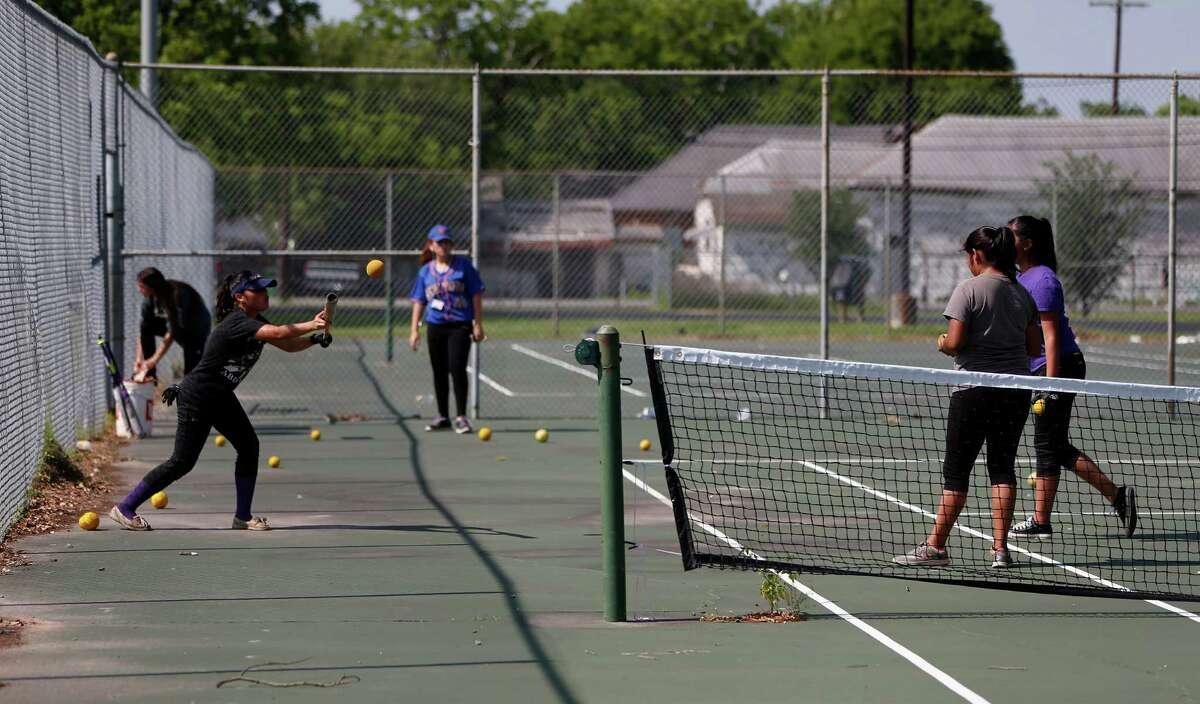 Members of the Davis High School softball team practice on the tennis courts, Wednesday, April 27, 2016, in Houston. The team was forced to practice on or near the tennis courts because the football team was practicing on the main field. ( Karen Warren / Houston Chronicle )