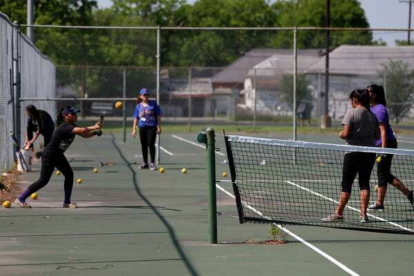Members of the Davis High School softball team practice on the tennis courts, Wednesday, April 27, 2016, in Houston. The team was forced to practice on or near the tennis courts because the football team was practicing on the main field.