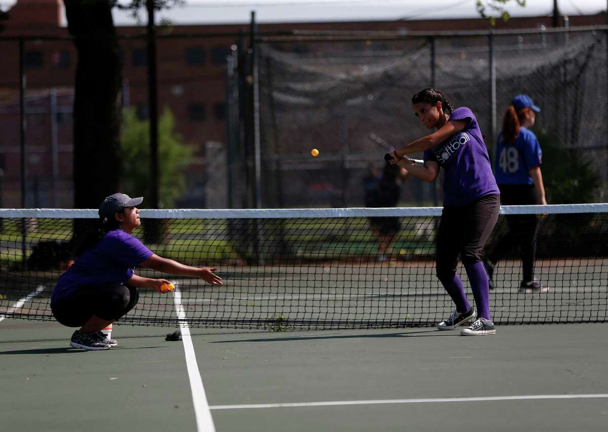 Mia Medrano, tosses a small whiffle ball to Monica Moreno, both 17, while on the tennis courts during the Davis High School softball team practice, Wednesday, April 27, 2016, in Houston. The team was forced to practice on/near the tennis courts because the football team was practicing on the main field.