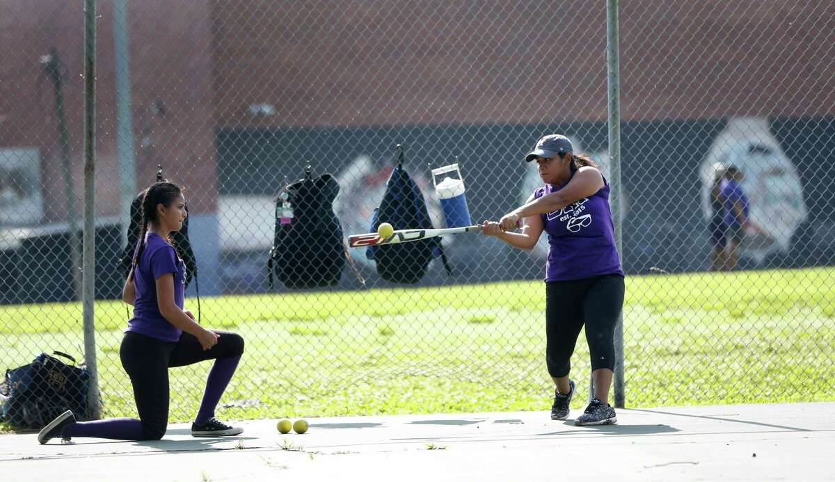 Monica Moreno, left, tosses a small whiffle ball to Mia Medrano, both 17, while on the tennis courts during the Davis High School softball team practice, Wednesday, April 27, 2016, in Houston. The team was forced to practice on/near the tennis courts because the football team was practicing on the main field.