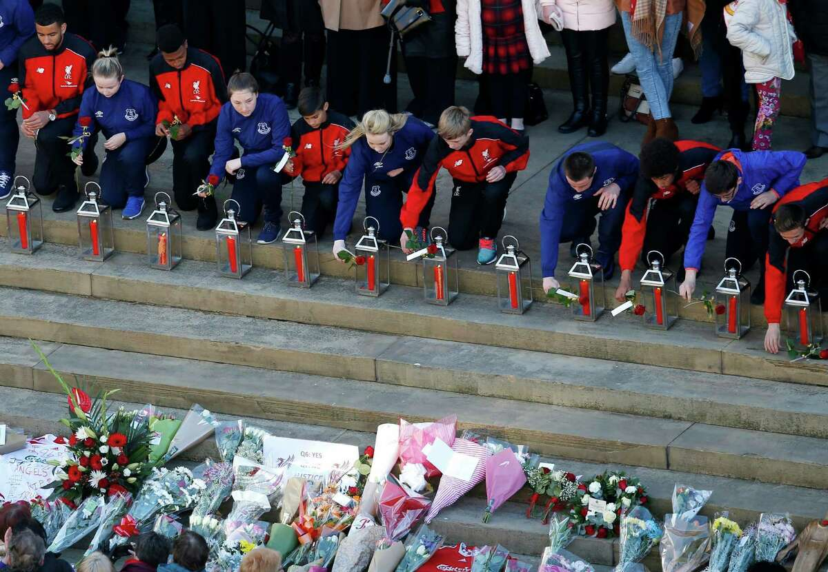 Representatives (96 in total) of Liverpool Football Club and Everton Football Club lay roses next to lanterns containing candles at a commemorative event at St George's Hall in Liverpool, England, Wednesday April 27, 2016, to mark the outcome of the Hillsborough inquest which ruled that 96 Liverpool fans who died as a result of the Hillsborough disaster on April 15, 1989, were unlawfully killed. (Peter Byrne/PA via AP) UNITED KINGDOM OUT NO SALES NO ARCHIVE