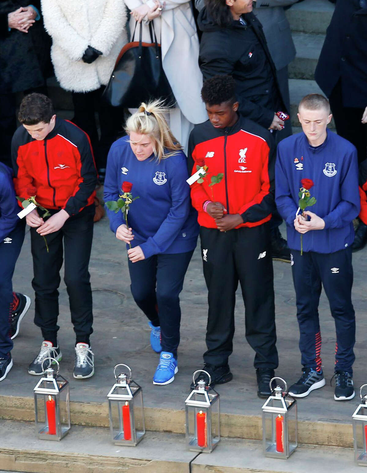 Representatives (96 in total) of Liverpool Football Club and Everton Football Club prepare to lay roses next to lanterns containing candles at a commemorative event at St George's Hall in Liverpool, England, Wednesday April 27, 2016, to mark the outcome of the Hillsborough inquest which ruled that 96 Liverpool fans who died as a result of the Hillsborough disaster on April 15, 1989, were unlawfully killed. (Peter Byrne/PA via AP) UNITED KINGDOM OUT NO SALES NO ARCHIVE