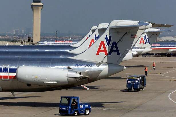 Workers, at right, guide an American Airlines plane as it leaves a gate at Dallas/Fort Worth International Airport in Grapevine, Texas, Wednesday, Sept. 19, 2001. American Airlines announced a massive restructuring Tuesday, Aug. 13, 2002, that will cut the size of its work force by 6 percent in an effort to make the world's biggest carrier competitive with lower-cost rivals. American, which said the plan is critical to its long-term survival, will cut 7,000 jobs, reduce its capacity by 9percent and retire its entire fleet of 100-seat Fokker planes as it struggles to end its huge losses. (AP Photo/Donna McWilliam)