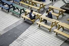 Employees look at their smartphones while sitting on the campus of a Pegatron Corp. factory in Shanghai, China, on Friday, April 15, 2016. This is the realm in which the world's most profitable smartphones are made, part of Apple Inc.'s closely guarded supply chain. Photographer: Qilai Shen/Bloomberg