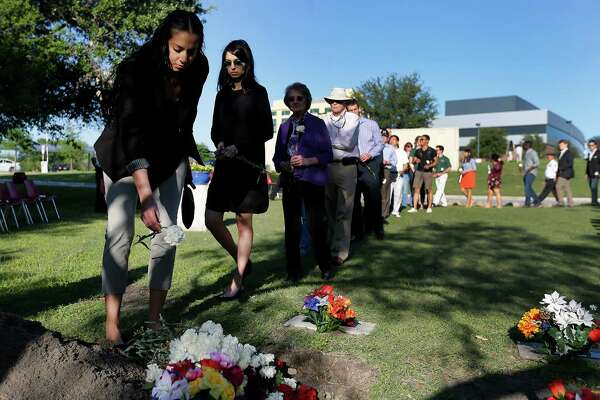 Guests place flowers and soil on a memorial honoring individuals who donated their bodies to the University of Texas Health Science Center during the school's annual ceremony on Wednesday, Apr. 27, 2016. The event honored the human donors used in the education of students at UTHSC and took place at Memorial Park near The Robert F. McDermott Clinical Science building at Greehey Academic & Research Campus. Student representatives from the Health Science Center's schools gave brief speeches about the anatomy lessons and life lessons they have learned from their first patients, the deceased human donors who altruistically gave their bodies to science. An AirLife helicopter flyover commenced the ceremony, songs by UTSA graduate vocal students, and the Fort Sam Houston Memorial Detachment Services unit performed the presentation of the flag in memory of body donors who served in the military. About 200 medical students along with donors' families attended the event.