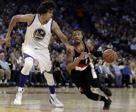 Portland Trail Blazers' Damian Lillard, right, drives the ball against Golden State Warriors' Anderson Varejao (18) during the first half of an NBA basketball game Sunday, April 3, 2016, in Oakland, Calif. (AP Photo/Ben Margot)