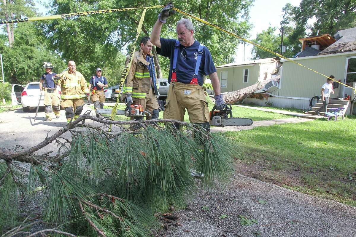 Klein volunteer firefighters helped clear debris at a Tomball-area subdivision, where a woman was killed in her home by a fallen tree Wednesday.