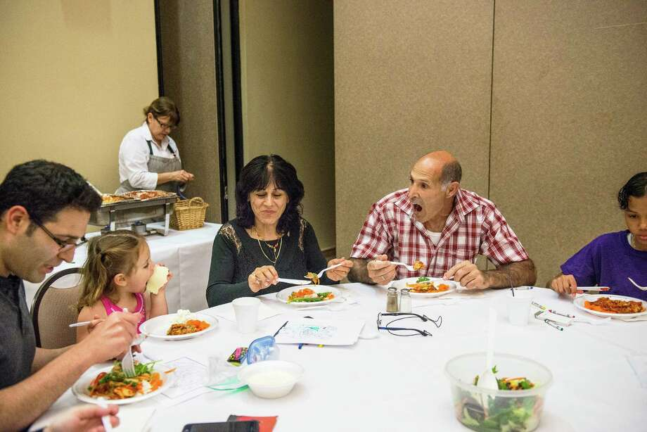 Siren Davis, center, talks to her eldest daughter Carlie, 6, left, while her younger daughter Maisie, 3, and husband Chip, right, enjoy a Passover meal of Matzah lasagna at Barshop Jewish Community Center of San Antonio on Wednesday, April 27, 2016. The center put on the meal as a way of supporting their community during the stricter dietary days of Passover. Photo: Matthew Busch, For The San Antonio Express-News / © Matthew Busch
