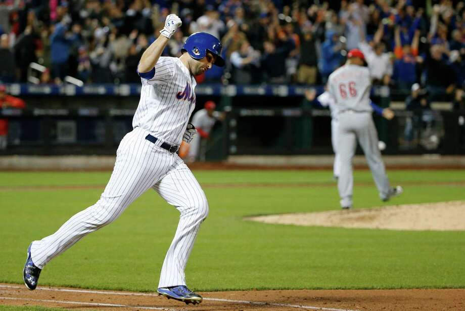 New York Mets second baseman Neil Walker (20) celebrates running down the first base line after hitting a seventh-inning, two-run, home run off Cincinnati Reds relief pitcher JC Ramirez, right, in a baseball game, Monday, April 25, 2016, in New York. (AP Photo/Kathy Willens) ORG XMIT: NYM112 Photo: Kathy Willens / Copyright 2016 The Associated Press. All rights reserved. This m