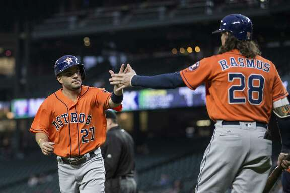 SEATTLE, WA - APRIL 27: Jos Altuve #27, left, of the Houston Astros is congratulated by teammate Colby Rasmus #28 after Altuve scored on a hit by Carlos Correa #1 of the Houston Astros during the third inning of a game against the Seattle Mariners at Safeco Field on April 27, 2016 in Seattle, Washington.
