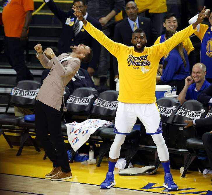 Golden State Warriors' Stephen Curry and Festus Ezeli enjoy a Klay Thompson 3-pointer in 3rd quarter against Houston Rockets in Game 5 of 1st Round of NBA Playoffs at Oracle Arena in Oakland, Calif., on Wednesday, April 27, 2016.